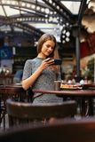 Woman In Cafe Taking Food Photo On Mobile Phone. Attractive Girl Making Photos In House. High Resolution royalty free stock photography
