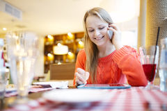 Woman in cafe with touchpad and phone Stock Images