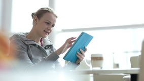 Woman in cafe using her touchpad. Young woman using her touchpad while drinking coffee in cafe stock video footage