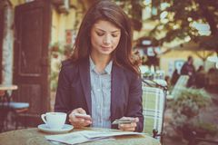 Woman at cafe, using phone to check credit card. stock images
