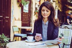 Woman at cafe, using phone to check credit card. stock photography