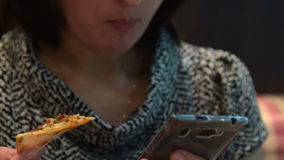 Woman in cafe using smart phone and eating pizza. Young woman using cellphone when eating pizza in the cafe. Having meal and browsing web stock video footage