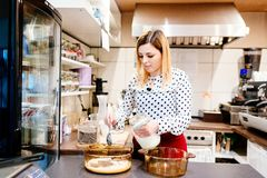 Woman cafe worker adding sugar to bowl with dessert. Ingredients stock photos