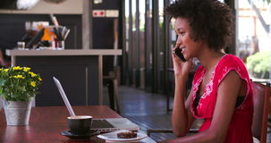 Woman In Cafe Working On Laptop And Answering Phone. Woman sitting at table in cafe working on laptop before answering mobile phone call. Shot in 4k on Sony stock video