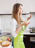 Woman  with cakes and tea in  kitchen Stock Images