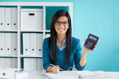Woman calculates tax at desk in office Royalty Free Stock Photos