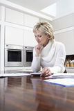 Woman Calculating Domestic Bills With Calculator In Kitchen Stock Photos