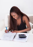 Woman Calculating Finance At Home Royalty Free Stock Image