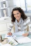 Woman calculating finances. Smiling woman calculating finances at home, checking bills, counting money Stock Photos