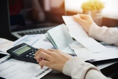 Woman calculating her Debt. Close up of woman hand calculating her monthly expenses with calculator.  Debt Stock Photography