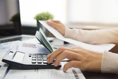 Woman calculating her Debt. Close up of woman hand calculating her monthly expenses with calculator.  Debt Royalty Free Stock Image