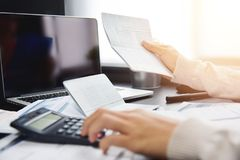 Woman calculating her Debt. Close up of woman hand calculating her monthly expenses with calculator.  Debt. Bank account Royalty Free Stock Image