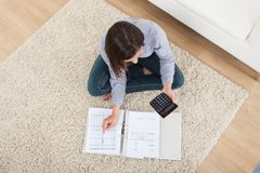 Woman calculating home finances on rug Stock Image