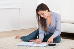 Woman Calculating Home Finances On Rug Royalty Free Stock Image