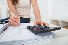 Woman calculating home finances at table. Midsection of young woman calculating home finances at table Royalty Free Stock Photos
