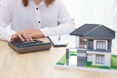Woman calculating about installment price with estate loan agree. Ment document and home model stock image