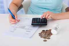 Woman calculating invoice by coins and thermostat at desk Stock Photos