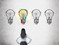 Woman calculating probability of good event. Woman with black hair standing with her back to viewer looking at four light bulb doodles drawn on wall. Only one of stock illustration