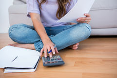 Woman calculating receipts lying on the floor Royalty Free Stock Images