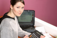 Woman with calculator. Girl, young woman with laptop and calculator- over pink stock photo