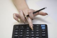 Woman and the calculator. The effective manicure does not hindrance calculations Royalty Free Stock Images