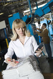 Woman With Calculator Checking Newspaper In Factory Royalty Free Stock Images