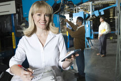 Woman With Calculator Checking Newspaper In Factory Royalty Free Stock Photos