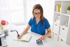 Woman with calculator and notebook at office Royalty Free Stock Images