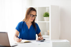 Woman with calculator and notebook at office. Business, people and bookkeeping concept - woman with calculator counting and writing to notebook at office stock photography
