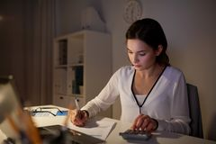 Woman with calculator and papers at night office. Business, accounting, overwork, deadline and people concept - woman with tax form and calculator working at Stock Images
