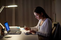 Woman with calculator and papers at night office. Business, accounting, overwork, deadline and people concept - woman with tax form and calculator working at Royalty Free Stock Image