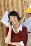 Woman On Call With Architect In Background Stock Photography