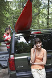 Woman On Call As Man Tie Kayak On Car Roof Stock Images