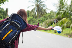 Woman call a car. Asian girl backpack in the road and forest background Royalty Free Stock Photos