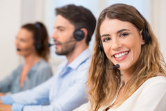 Woman at call centre. Smiling female call centre operator doing her job with a headset while looking at the camera. Portrait of happy women in a call center stock images