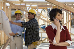 Woman On Call With Contractors In Background Stock Image