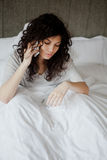 Woman call in sick. In the morning from her bed Stock Photography