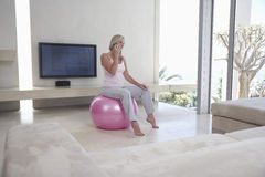 Woman On Call While Sitting On Fitness Ball Royalty Free Stock Photos