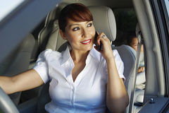Woman On Call With Son Sitting On Backseat. Happy business women communicating on cell phone with son sitting on backseat stock photography