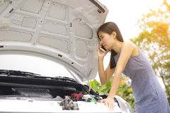 A woman is calling a car mechanic because her car is broken. Royalty Free Stock Photo