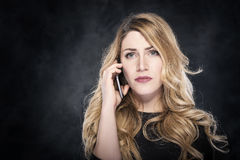 Woman calling with a cell phone. Woman calling with a cell phone over dark background Stock Photos