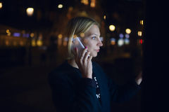 Woman calling with cell telephone and using city computer for touristic information while standing at night on the street Stock Images