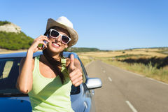 Woman calling on cellphone during summer car travel. Successful happy woman on cellphone call enjoying summer car travel vacation and doing approval positive Royalty Free Stock Photos