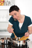 Woman is calling and cooking Stock Photo