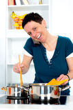Woman is calling and cooking Stock Photography