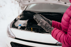 Woman calling for help or assistance - winter car breakdown. Young woman calling for help or assistance after her car breakdown in the winter. Broken down car Stock Image