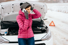 Woman calling for help or assistance - winter car breakdown. Young woman calling for help or assistance after her car breakdown in the winter. Broken down car Stock Photo