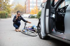 Woman Calling For Help Near Unconscious Cyclist Lying On Street stock images