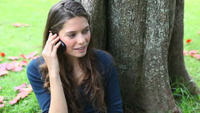 Woman calling leaning against a tree. Video of a woman calling leaning against a tree stock video