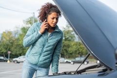 Woman calling mechanic service after vehicle problem royalty free stock photography